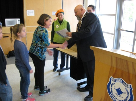 "Mayor Corkum hands out copies of ""Pumpkin People"" to Grade 3 students while Sandra looks on."